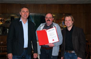 Johannes Strauch (links) und Martin Mertens (rechts) überreichen Paul-Rolf Essel die Urkunde